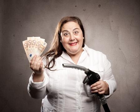 fuel crisis: woman holding a fuel pump nozzle