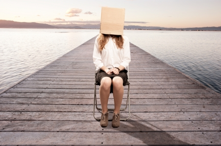 inconspicuous: woman sitting on a wharf with a box in her face
