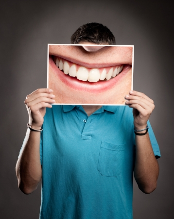 young man holding a picture of a mouth smiling Stockfoto