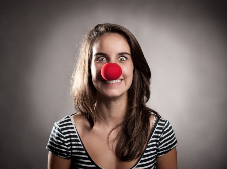 clown's nose: happy young girl with a clown nose