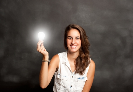 lady with the lamp: young woman holding a lightbulb in front of chalkboard