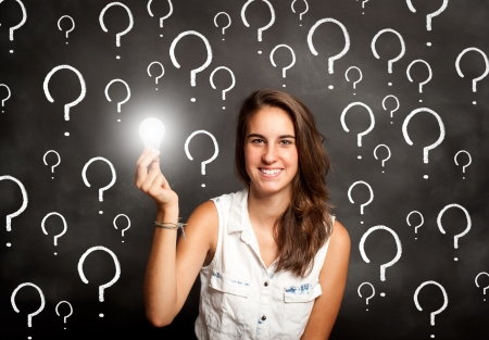 young woman holding a lightbulb in front of chalkboard with interrogation symbols Stockfoto