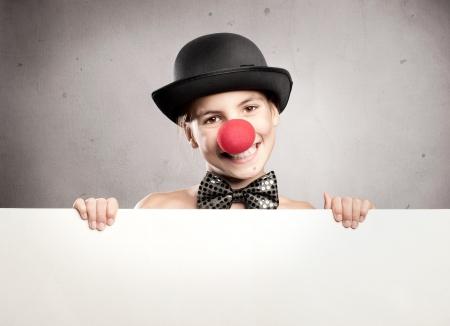 nariz roja: niña feliz con una nariz de payaso, con un cartel Foto de archivo