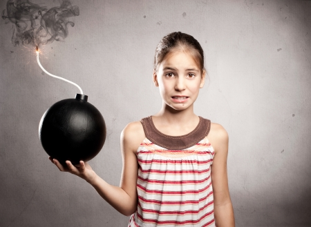 scared little girl holding an old-fashioned bomb Stockfoto