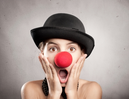 portrait of surprised little girl with a clown nose