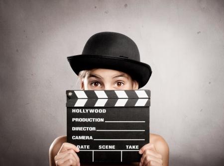 bambina in possesso di un bordo di valvola di film su uno sfondo grigio