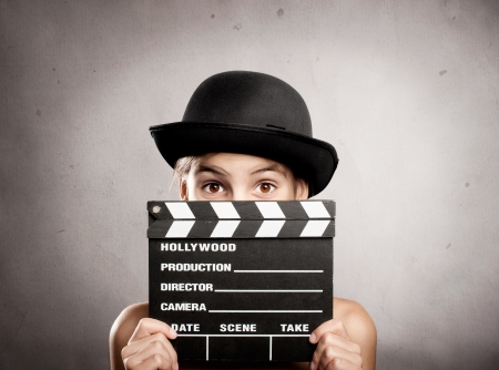 little girl holding a movie clapper board on a grey background photo