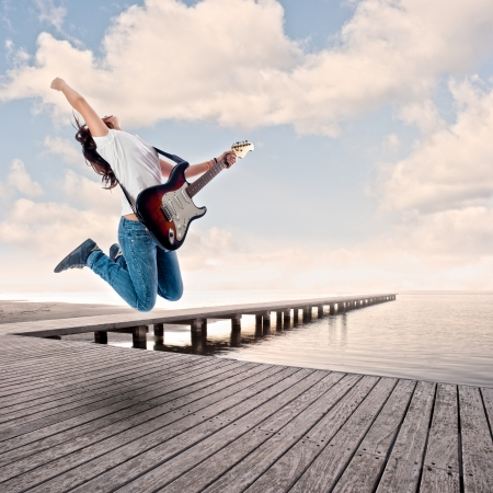 air guitar: teenager girl playing electric guitar and jumping on a wharf Stock Photo