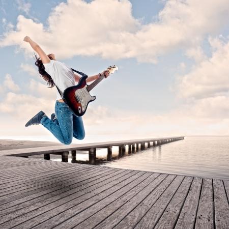 tiener meisje spelen elektrische gitaar en springen op een werf Stockfoto