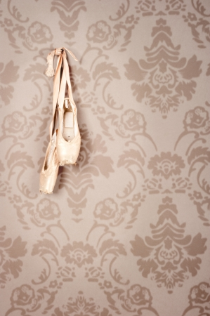 ballet slipper: pair of old ballet shoes hanging on a wall