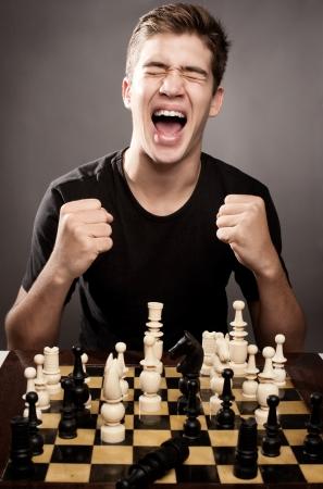 Gelukkig jonge man viert schaken winnen