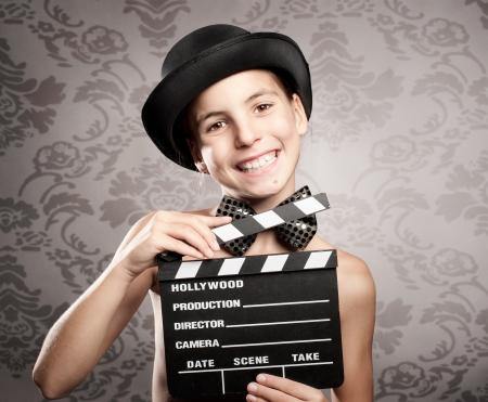 gelukkig meisje bedrijf een film klepel bord op een grijze achtergrond