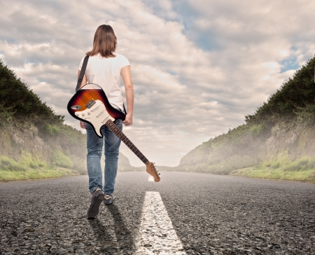 young musician woman with an electric guitar walking on a road photo