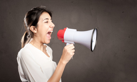 young woman shouting with a megaphone on a gray background Stock Photo - 25722231