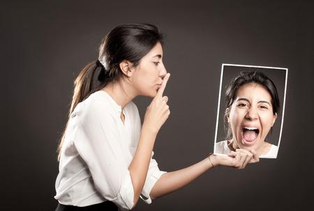 vrouw blijkt stilte gebaar en die een portret van zichzelf Stockfoto