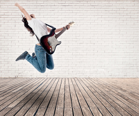 teenager girl jumping with electric guitar on a room Stock Photo