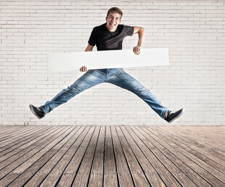 attractive young man jumping with a white banner on a room with white bricks wall and wood floor photo