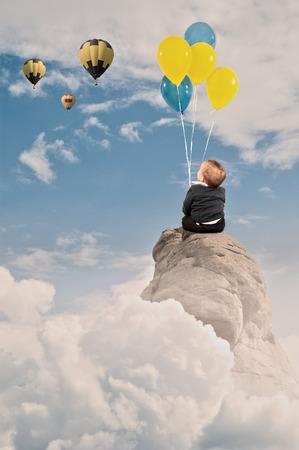 jongetje bedrijf stelletje ballonnen plaatsing op de top van een berg Stockfoto