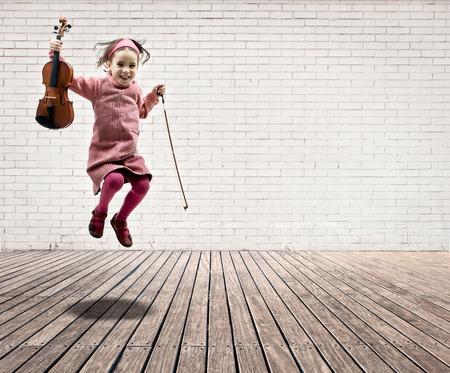 흰색 벽돌 벽과 나무 바닥이있는 방에 바이올린 점프 어린 소녀