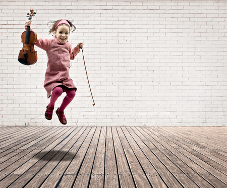 violin: little girl with violin jumping on a room with white bricks wall and wood floor