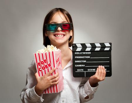 little girl wearing 3D glasses and eating popcorn photo