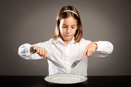little hungry girl sitting at table holding forks in front of a plate