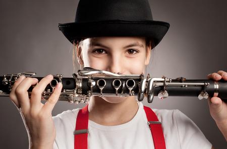meisje spelen klarinet op een grijze muur