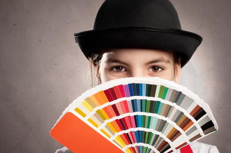 little girl holding a pantone palette on a gray wall Standard-Bild