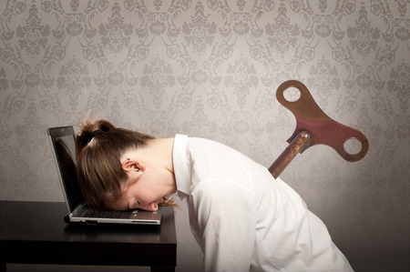businesswoman with a key winder on her back sleeping on laptop photo