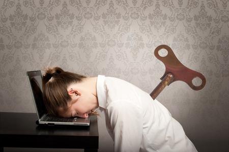 durmiendo: mujer de negocios con una bobinadora clave en su espalda para dormir en la computadora portátil Foto de archivo
