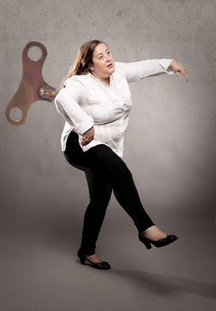 businesswoman with wind up  key in her back on a gray wall  photo