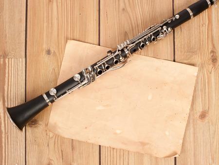 clarinete: clarinete y el papel en blanco en la mesa de madera