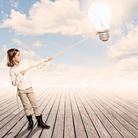 klein meisje met een lamp met een touw op een werf