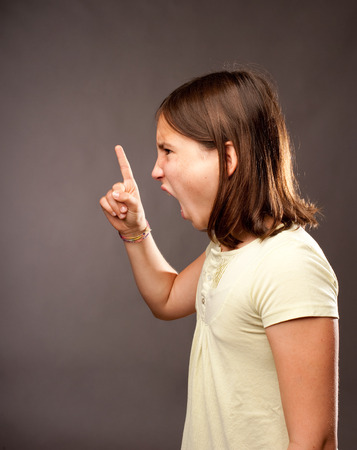 portrait of angry girl on gray background Stock Photo