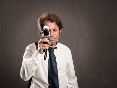 businessman with retro film camera on gray background photo