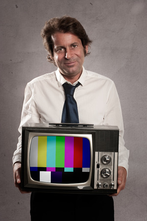 businessman with old retro television on gray background photo