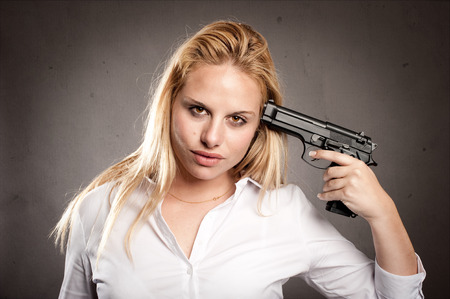 holding gun to head: woman shooting herself with a gun on gray background Stock Photo