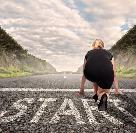 start position: businesswoman on a road ready to run. Motivation concept