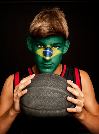 portrait of basketball player with brazilian flag painted on his face photo