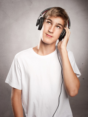 one eye closed: young man wearing headphones listening to music on grey background