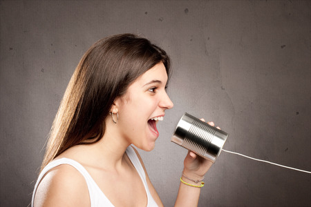 tin can telephone: young woman using a can as telephone on a gray background Stock Photo