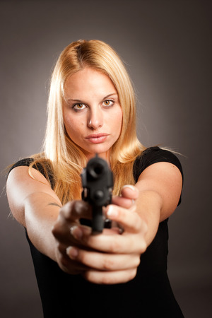 woman with a gun on gray background