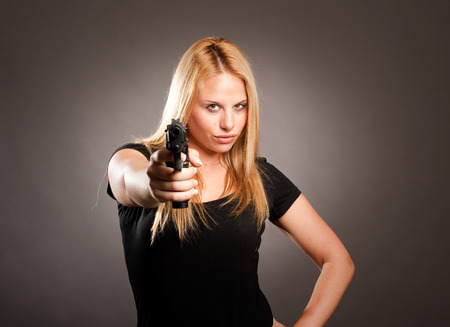 holding gun to head: woman with a gun on gray background