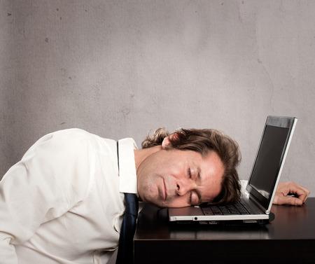 cansancio: hombre de negocios que duerme en la computadora port�til sobre fondo gris