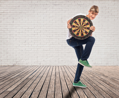 young man holding a dartboard on a room with white bricks wall and wood floor photo