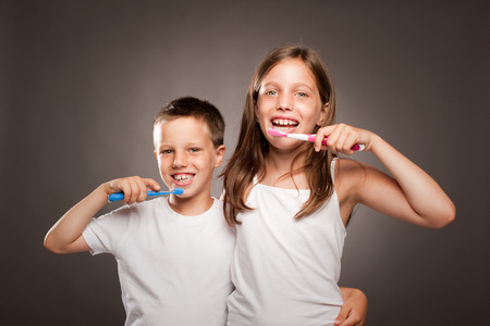 children brushing her teeth on a gray background Stock Photo
