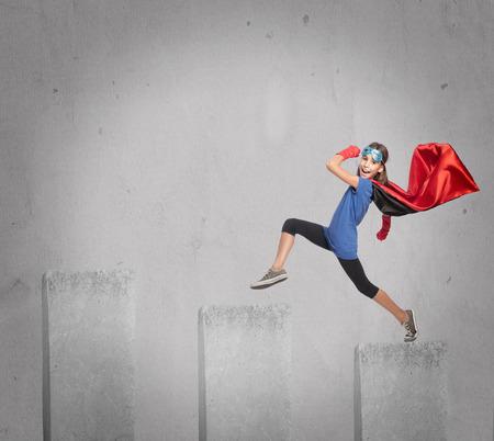 little girl wearing a superhero costume walking on a growing chart