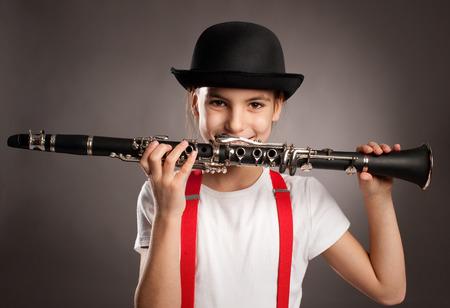 clarinete: ni�a tocando el clarinete en un fondo gris