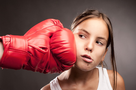 woman with boxing gloves: little girl and red boxing globe  hitting her face Stock Photo