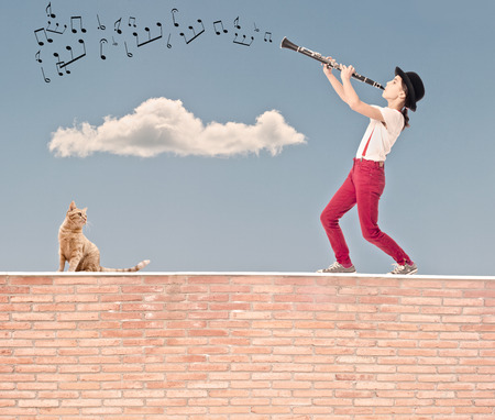 little girl playing clarinet on the top of a bricks wall Standard-Bild